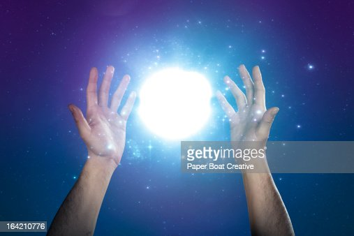 hand supporting abstract glow of light and stars  Stock Photo