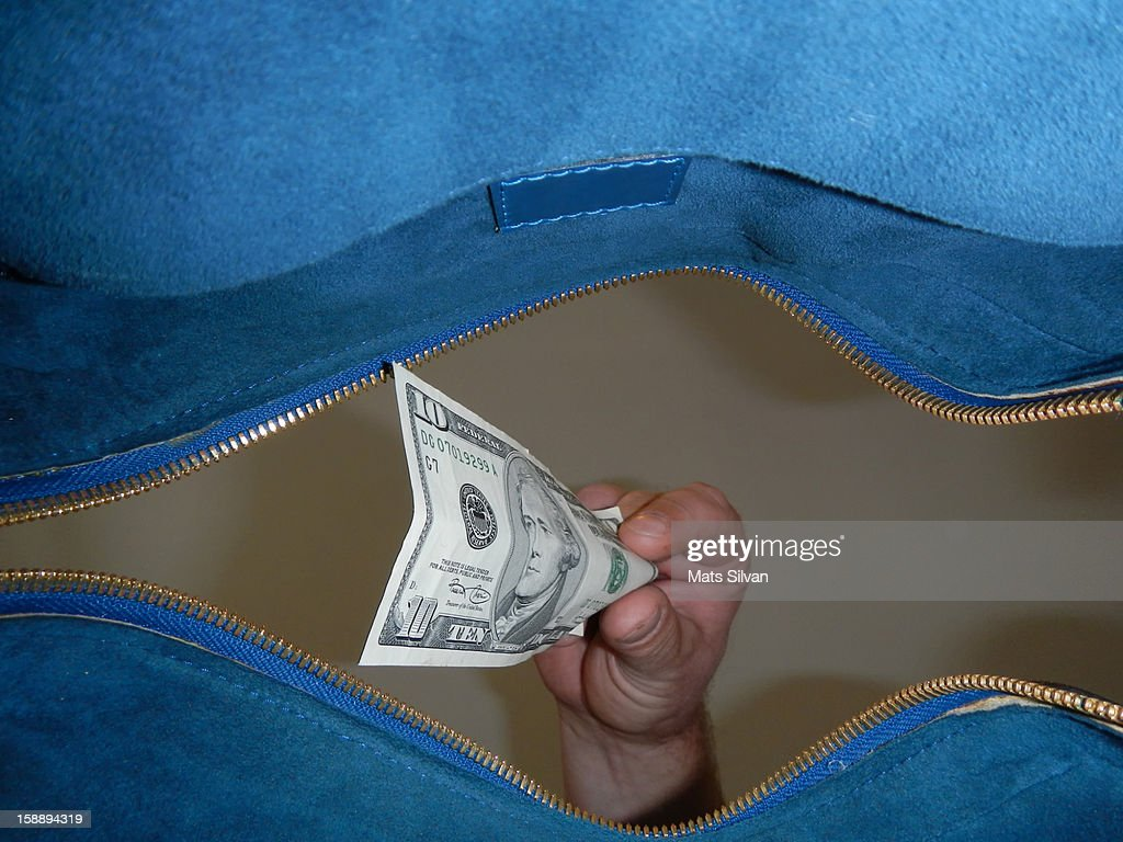 Hand takes money from a bag : Stock Photo