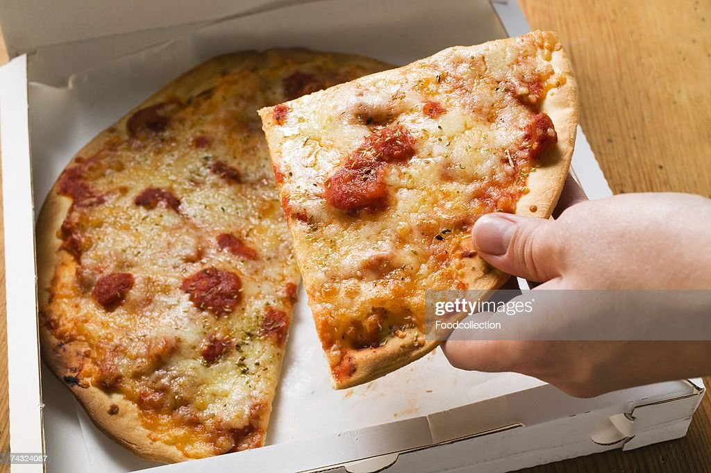Hand taking a slice of pizza Margherita out of pizza box : Stock Photo