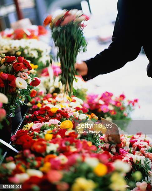 Hand taking bunch of flowers from stall in street (blurred motion)