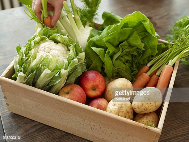 Hand taking crate with fresh fruit and vegetables