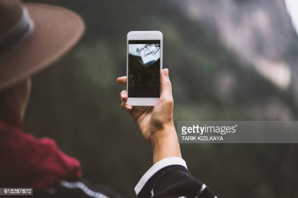 Hand taking photo of scenic mountain view