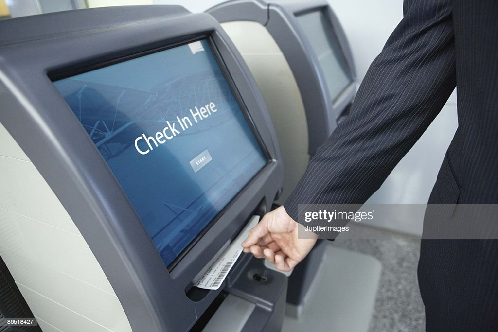 Hand taking ticket from automated check in machine