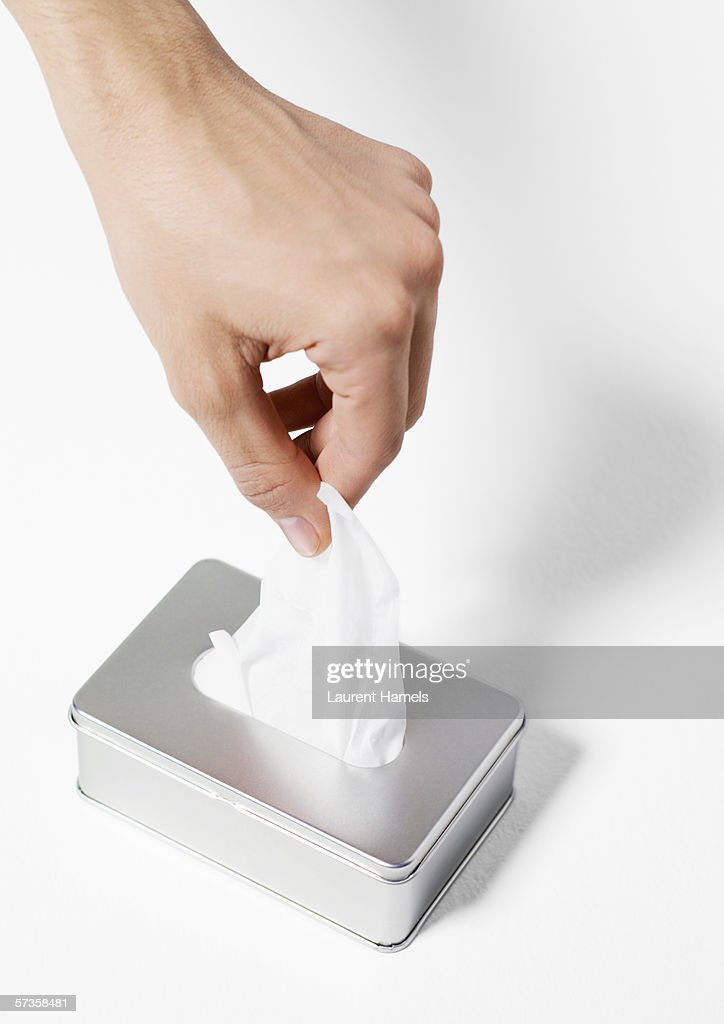 Hand taking tissue from dispenser