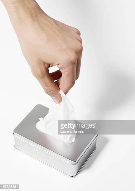 Hand taking tissue from dispenser