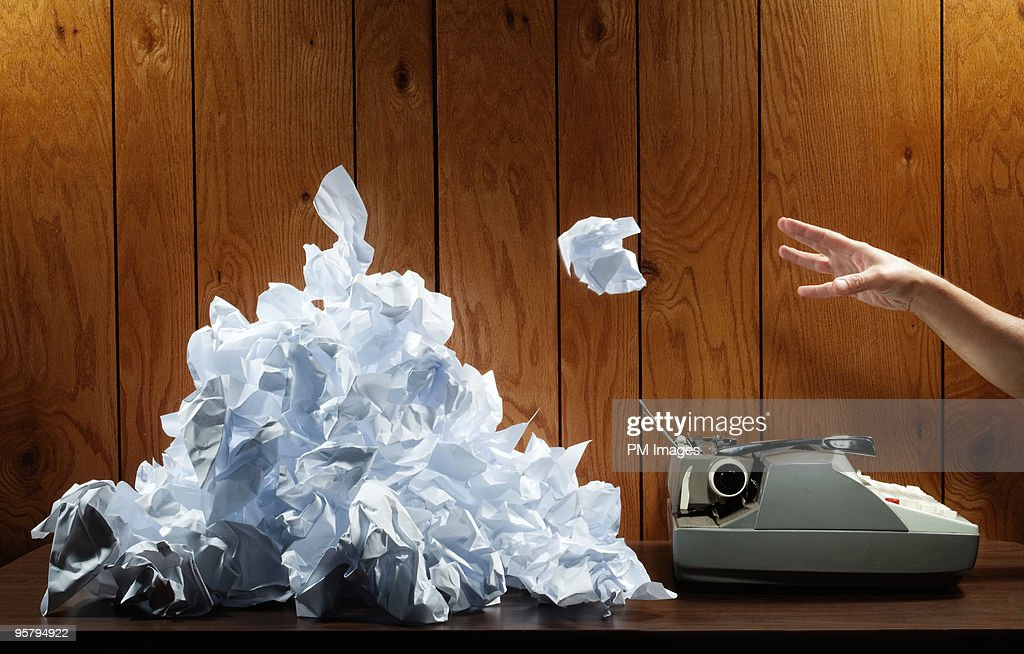 Hand throwing crumpled paper into a pile