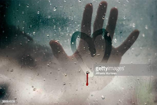 Hand touching a broken heart on a rainy window