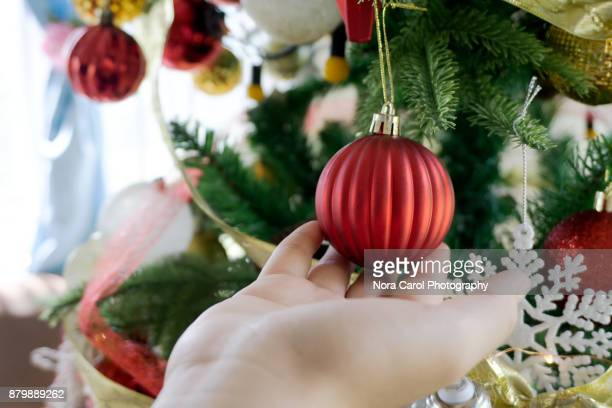 Hand Touching A Christmas Bauble on a Tree