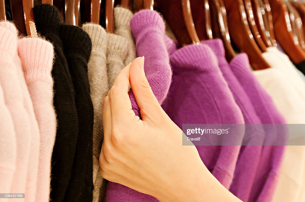 Hand touching cashmere sweater on clothing rack : Stock Photo