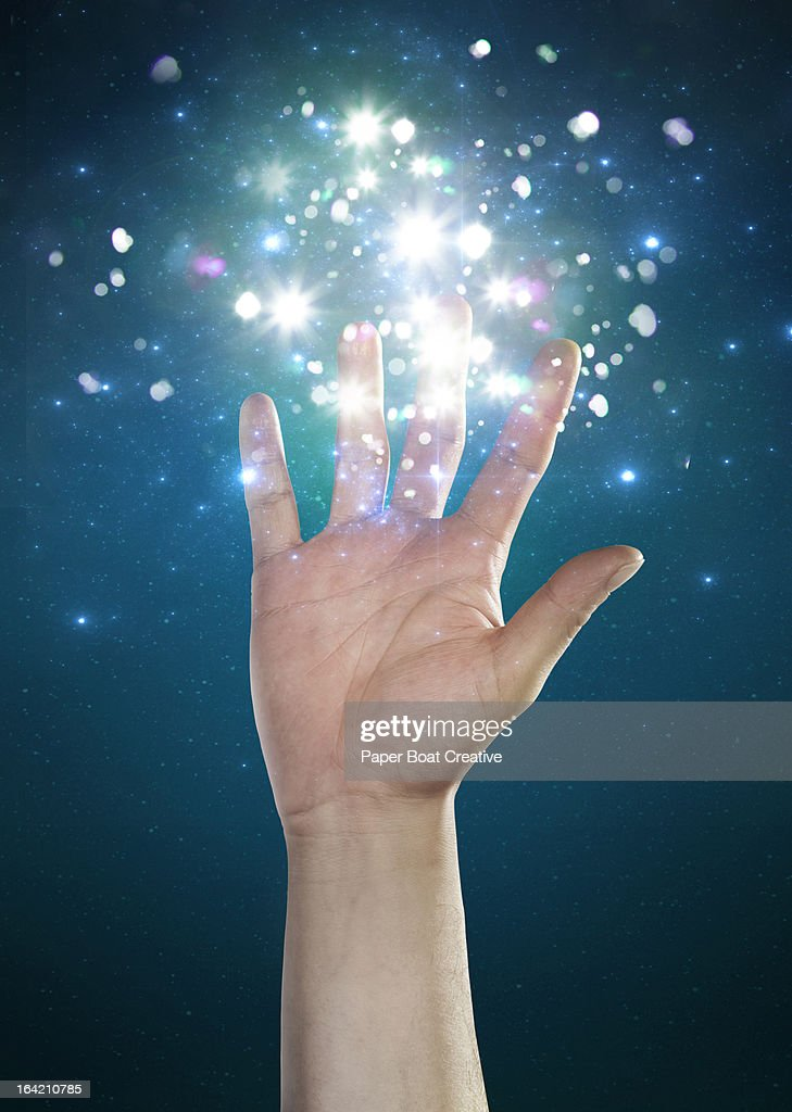 hand touching sparkles and abstract glow : Stock Photo