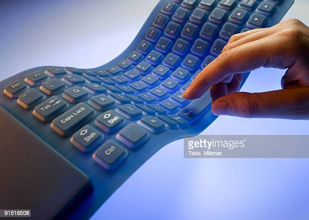 A hand typing on a flexible keyboard
