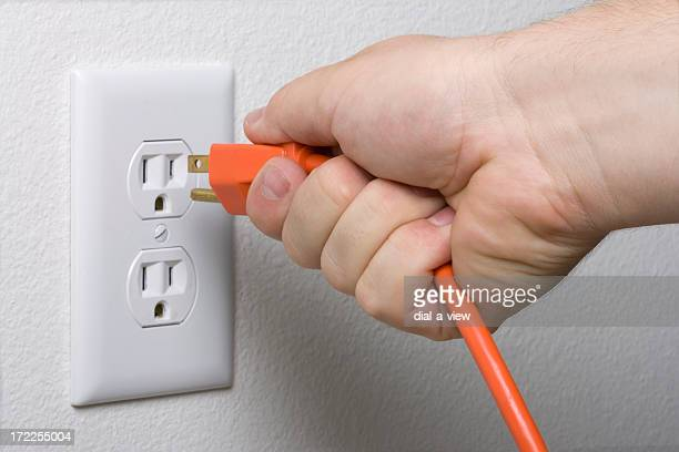 A hand unplugging an orange cord from a white outlet