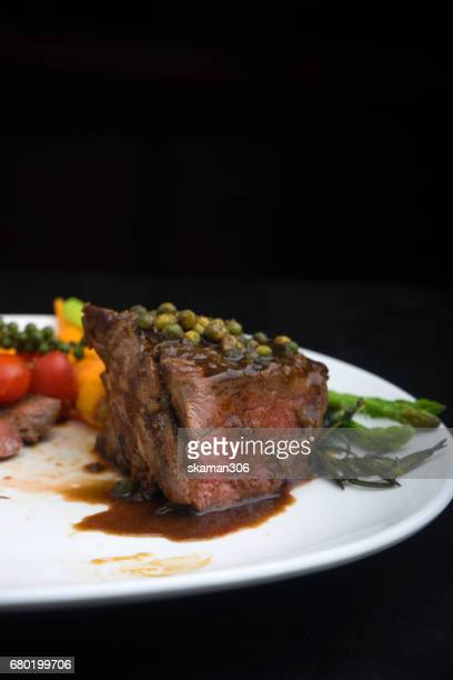 hand use Fork and knife cut tenderloin beef steak with vegetable