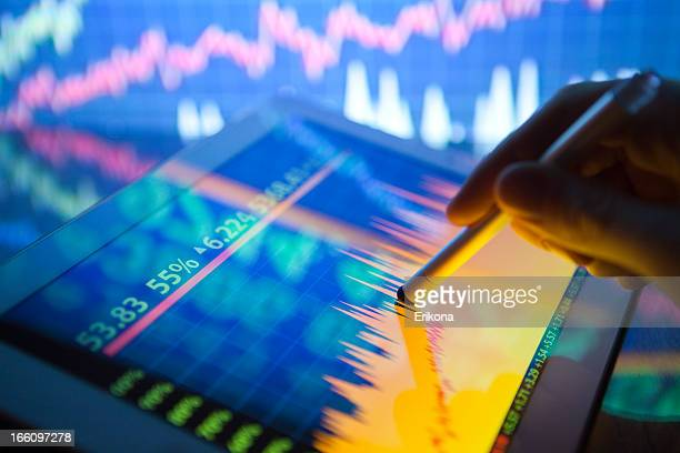 A hand using a digital tablet showing stock fluctuations