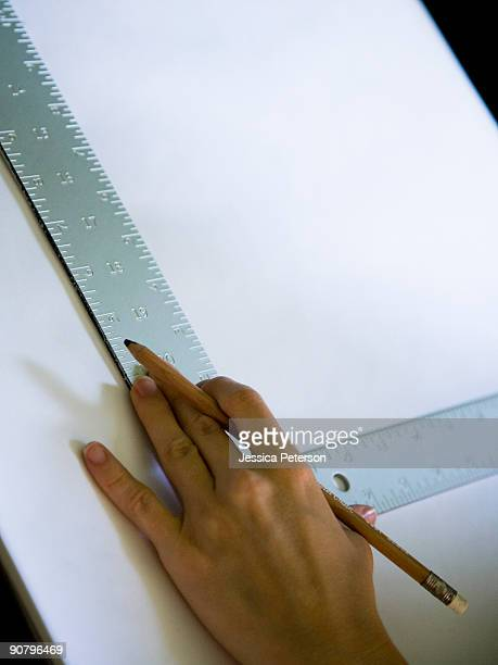 hand using a square on a drafting table