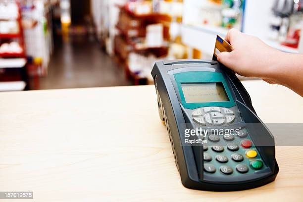 Hand using smart card reader with store in background