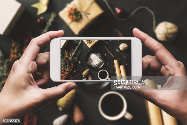 Hand using smartphone, sharing Christmas flat lay on social media