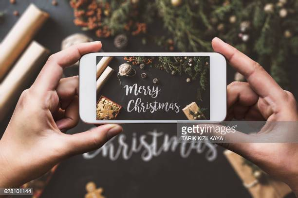 Hand using smartphone, sharing Christmas preparation on social media