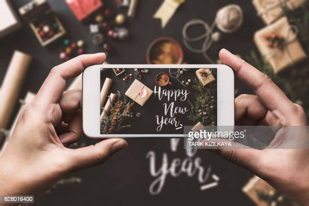Hand using smartphone, sharing new Year preparation on social media