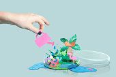 Hand watering a paper craft world in petri dish