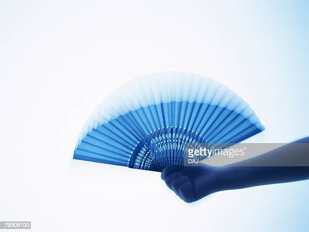 A hand waving a Japanese fan, Close Up, Blurred Motion, Toned Image, Silhouette