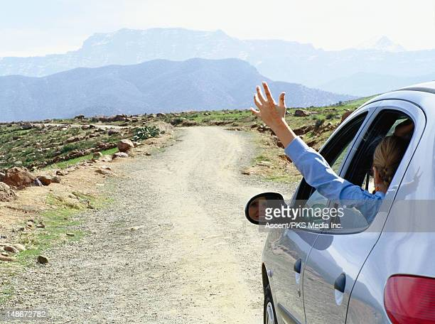 Hand waving out of car window.