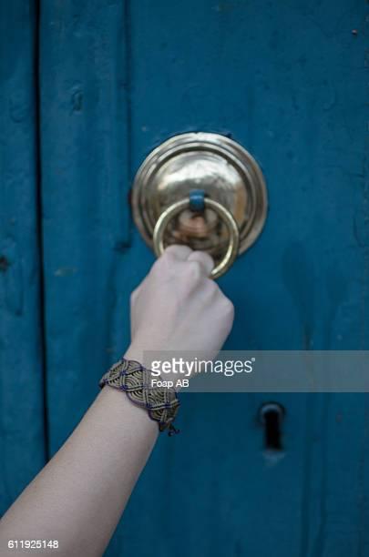 Hand wearing bracelet knocking door