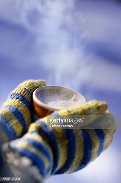 Hand wearing mittens, holding mug of cocoa, close-up