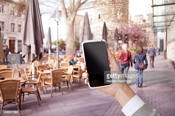 Hand with a smart phone in street by a café