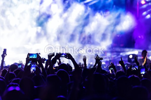 Hand with a smartphone records live music festival : Stock Photo