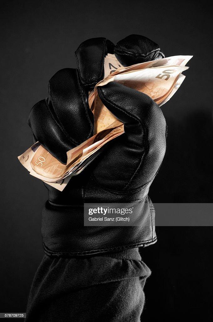 Hand with black glove grabbing money