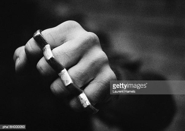 Hand with brass knuckles, close-up, b&w