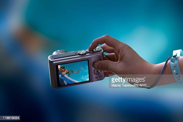 Hand with camera showing girl in pool