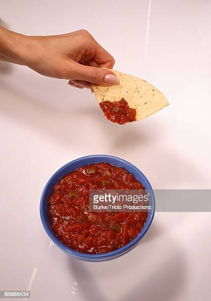 Hand with chip and salsa