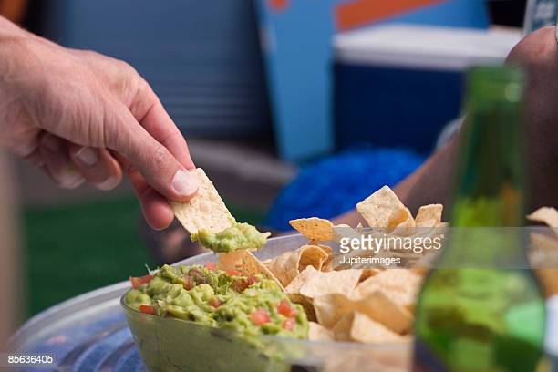Hand with chips and guacamole