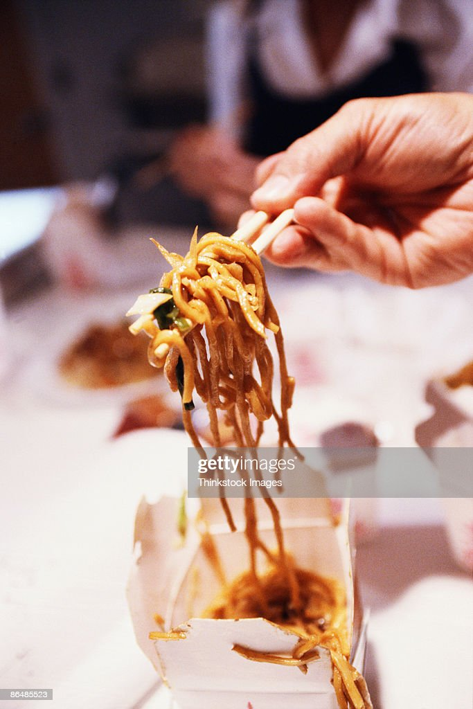 Hand with chopsticks and Chinese food : Stock Photo