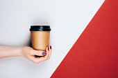 Hand with brown cup of coffee to go. Red and grey background with place for text.