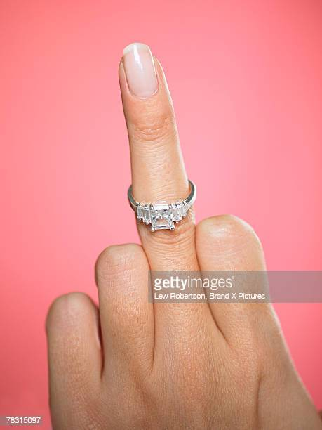 Hand with engagement ring making obscene gesture