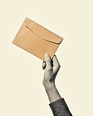 Hand with envelope from kraft paper, isolated, toned, black and white