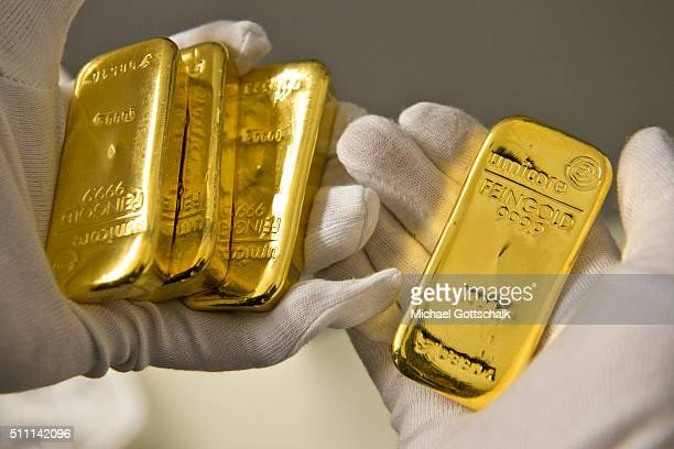 A hand with glove holds a gold bar in the safe of Pro Aurum Gold trading house on February 16 2016 in Muenchen Germany