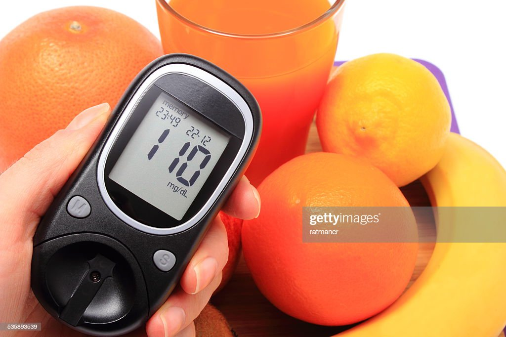 Hand with glucometer, fresh natural fruits, glass of juice : Stock Photo