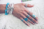closeup of young woman hand with lot of boho style jewelry, rings and bracelets outdoor summer day