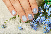 Hand with short manicured nails colored with gray nail polish and blue forget-me-not flowers