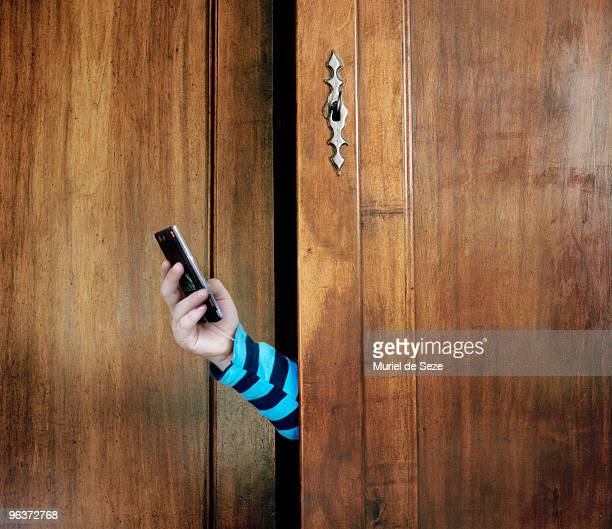 Hand with mobil phone in wardrobe