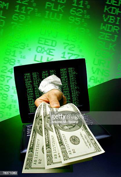 Hand with money and stock quotes in computer