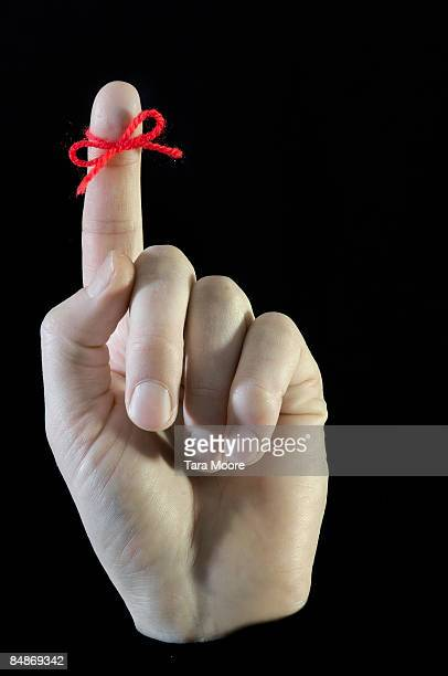 hand with red string tied around forefinger