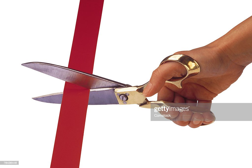 Hand with scissors cutting a ribbon