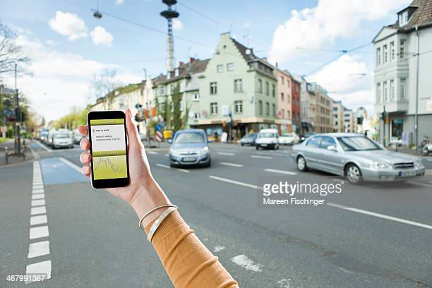 Hand with smart phone, CO2 emission app in street