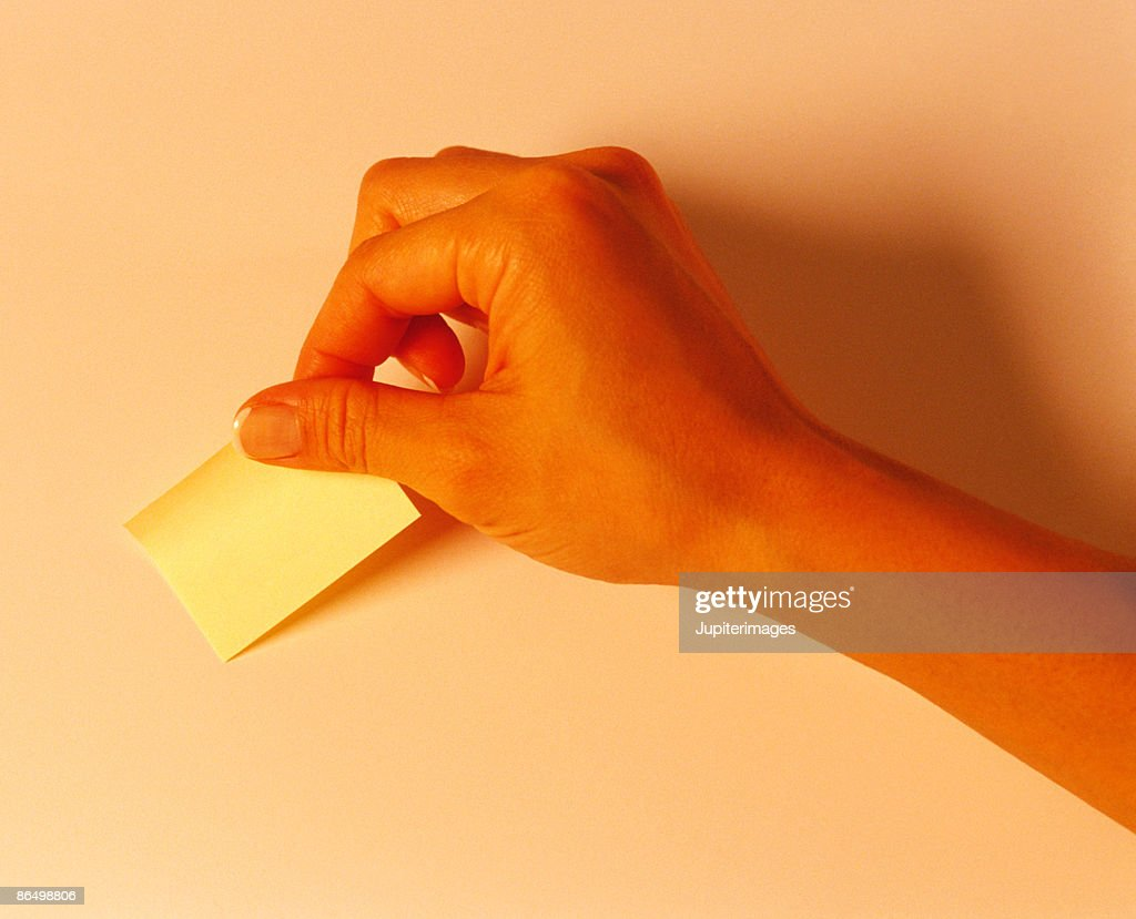 Hand with sticky note : Stock Photo