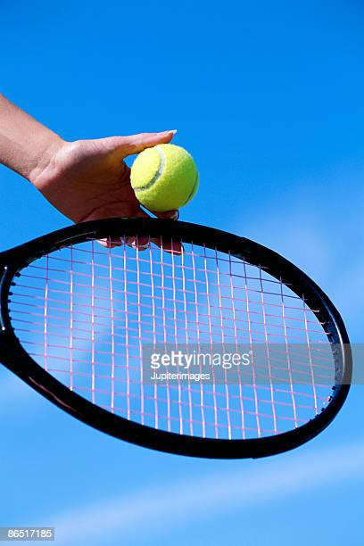 Hand with tennis ball and tennis racket